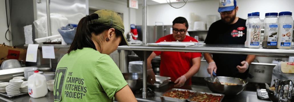 Three Campus Kitchen volunteers serve meals.
