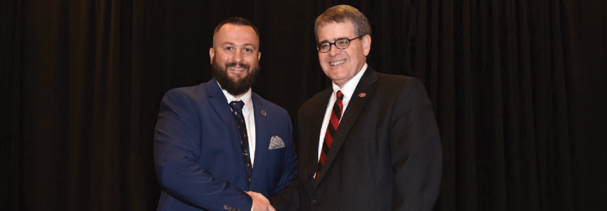 A graduating student veteran shakes hands with UGA President Jere W. Morehead at the 2019 Spring Honor Cord and Awards Reception.
